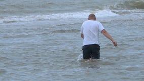 Mann steigt in das Meer ein stock video