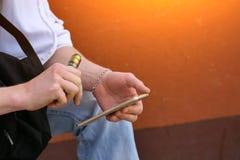 Mann steigt elektronische Zigarette beim Sitzen mit der Telefonnahaufnahme an stockfoto