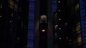 Mann steigt im Aufzug außerhalb des Gebäudes nachts ab stock video