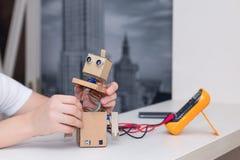 Mann stellt Roboter, die Verbindung aller Komponenten her Lizenzfreies Stockfoto