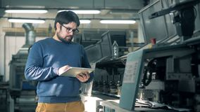 Mann steuert die Arbeit des typografischen Förderers und schreibt auf einer Tablette stock video