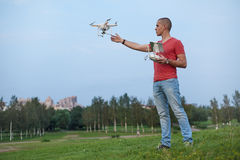 Mann steuert ein quadrocopter im Park lizenzfreie stockfotografie