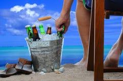 Mann am Strand mit einer Wanne Bier Stockfoto