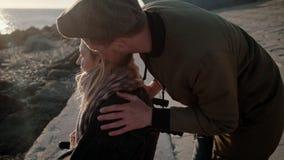 Mann streicht Kopf seiner geliebten Frau im Rollstuhl auf Seeküste stock footage