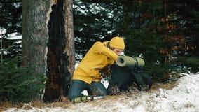 Mann sucht etwas in seinem Rucksack, der im Winterwald sitzt, der mit Schnee bedeckt wird stock footage