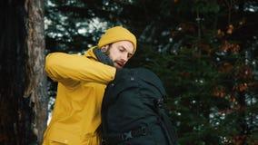 Mann sucht etwas in seinem Rucksack, der im Winterwald sitzt, der mit Schnee bedeckt wird stock video