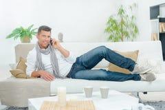 Mann am Telefon auf Couch Stockfotografie