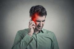 Mann am Telefon mit Kopfschmerzen Zelluläres bewegliches Strahlungskonzept stockfotografie