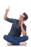 Mann am Telefon sitzt, zeigt u. schaut oben Lizenzfreie Stockbilder