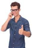 Mann am Telefon zeigt sich Daumen Lizenzfreies Stockbild