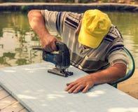 Mann am Tisch schnitt eine Spannvorrichtungssäge heraus stockfoto