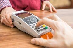 Mann trägt PIN zum Zahlungsanschluß ein Zahlen im Shop mit Kreditkarte Lizenzfreies Stockfoto