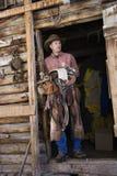 Mann-tragender Cowboyhut, der einen Sattel anhält Stockfotografie