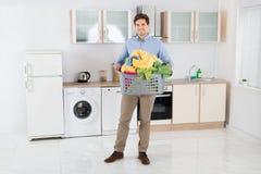 Mann-tragender Korb mit Haufen von Kleidung Lizenzfreie Stockfotos