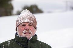 Mann-tragender Schnee bedeckte Kappe lizenzfreies stockfoto