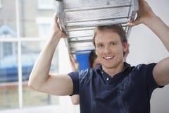 Mann-tragender Stehleiter mit der Frau, die in Unrenovated-Haus hilft Stockfoto