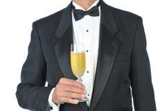 Mann-tragendes Smoking-Holding-Glas von Champagne Lizenzfreie Stockfotografie