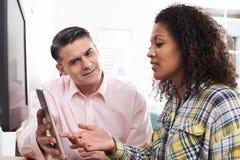 Mann-Trainings-Frau im Büro unter Verwendung Digital-Tablets Stockfotos