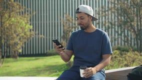 Mann in trinkendem Kaffee der Baseballmütze und surfendes Sitzen des Netzes auf Parkbank stock footage