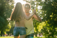 Mann turning woman while dancing Bachata in the sun Stock Photos