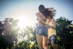 Mann turning woman dancing in the grass in summer park. Mann turning women dancing in the grass in summer park right before sunset royalty free stock image