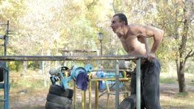 Mann tut Übungen des Liegestützes auf Stangen stock footage
