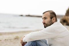 Mann u. x28; brunette& x29; mit einem Bart in einer weißen Strickjacke, die das s betrachtet lizenzfreie stockfotografie