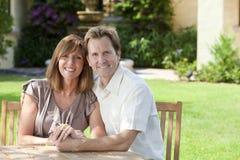 Mann-u. Frauen-verheiratetes Paar, das im Garten sitzt Stockfotografie