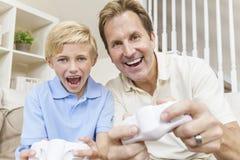 Mann u. Junge, Vater u. Sohn, Videospiele spielend Stockbild