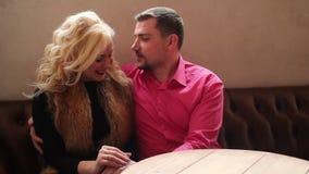Mann umarmt die jungen sexy Frauen, die auf der Couch sitzen stock footage