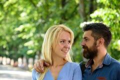 Mann umarmt glückliche blonde Freundin, setzte Hand auf ihre Schulter Lizenzfreie Stockfotos