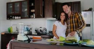 Mann-Umarmungs-Frauen-glückliche lächelnde Paare in der Küche, die zusammen kocht, bereiten gesundes Abendessen vor stock video footage