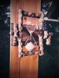 Mann umfaßt Magen von schwangere Frauen auf grauem Hintergrund mit gemaltem Hourglass Stockbild