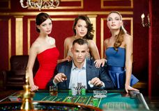 Mann umgeben durch Damenglücksspiel-Roulette Stockfotos