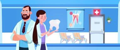 Mann-und Ärztin-Team Holding Tooth Over Dental-Büro-Innenzahnarzt-Hospital Or Clinic-Konzept Stockbild