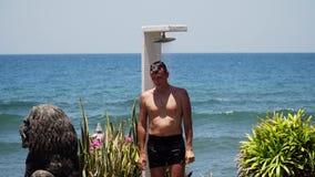 Mann und Dusche auf dem Strand
