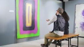 Mann und Frau überprüft abstraktes Bild in der Galerie und sitzt auf Bank stock video footage