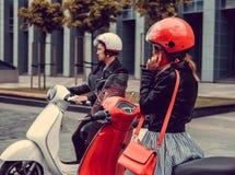 Mann und Frau auf Bewegungsrollern in einer Stadt Lizenzfreie Stockfotografie