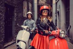 Mann und Frau auf Bewegungsrollern in einer Stadt Stockbild