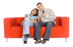 Mann und Frau auf Couch-überwachendem Fernsehen Lizenzfreie Stockbilder