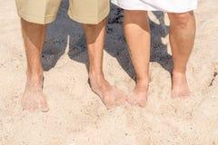 Mann und Frau auf dem Strand mit Füßen im Sand stockbilder