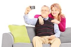 Mann und Frau auf einem Sofa, das Fotos von selbst mit Telefon macht Stockfotografie