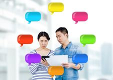 Mann und Frau auf Geräten mit glänzenden Chatblasen Lizenzfreie Stockbilder