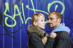 Mann und Frau bleibt nahe Graffitiwand lizenzfreie stockfotografie