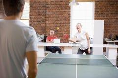 Mann und Frau in den Büroräumen, die Klingeln pong spielen Stockfotos