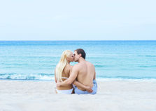 Mann und Frau in den Badeanzügen, die auf dem Strand sitzen und küssen Stockfoto