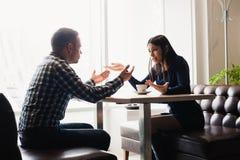 Mann und Frau in den Diskussionen im Restaurant Stockfotografie