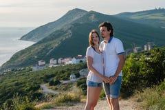 Mann und Frau in den hellen Hemden und in den kurzen Hosen, die auf einem Berg mit Meerblick stehen Front View Stockfoto