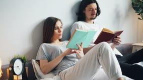 Mann und Frau in den Pyjamalesebüchern im Bett zu Hause, das Seiten dreht stock video footage