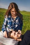 Mann und Frau, die auf dem Gras sitzen sein Kopf in ihrem Schoss Lizenzfreies Stockbild